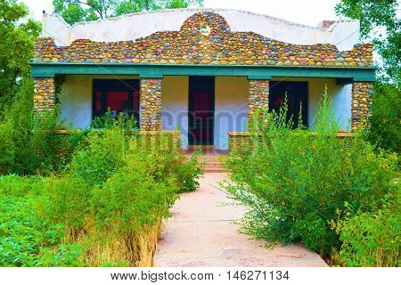 Abandoned adobe style home with overgrown plants caused by an economic depression