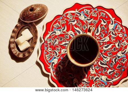 Patterned plate of coffee table with cup of morning drink and cubs of sugar