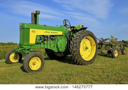 ROLLAG, MINNESOTA, Sept 1: A  Restored  John Deer 630 two cylinder tractor pulling a plow is displayed at the West Central Steam Threshers Reunion(WCSTR) where 1000s attend each Labor Day weekend in Rollag, MN each year.