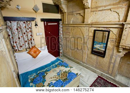 JAISALMER, INDIA - MAR 1, 2015: Poor interior design of a single room with a clean bed an indian hotel on March 1, 2015. Jaisalmer lies in the heart of the Thar Desert and has a population of about 78000.