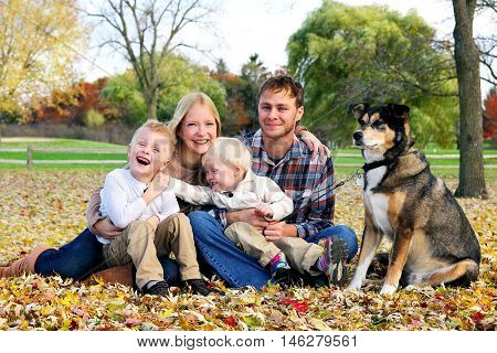 A happy family of four people and their pet dog are posing for a portrait in the fallen leaves in the park as their children goof around.