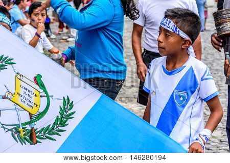 Antigua Guatemala - September 14 2015: Locals wave Guatemalan flags & wear patriotic headbands & shirts during Guatemalan Independence Day celebrations