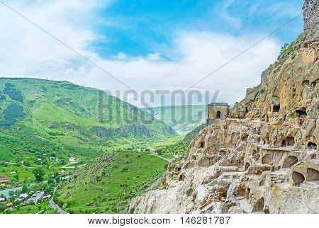 The medieval monastic settlement carved in rock is the perfect viewpoint overlooking the green valley with buildings of modern mountain resort Vardzia Samtskhe-Javakheti Region Georgia.