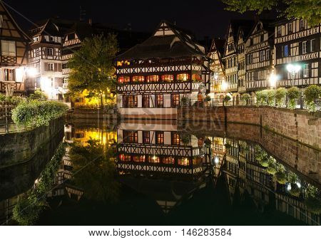 STRASBOURG, FRANCE. 31st August 2016. The Maison des Tanneurs on Benjamin Dix square, reflected in the waters of the River Ill by night. The restaurant is very popular with the many tourists who visit Strasbourg each Summer.