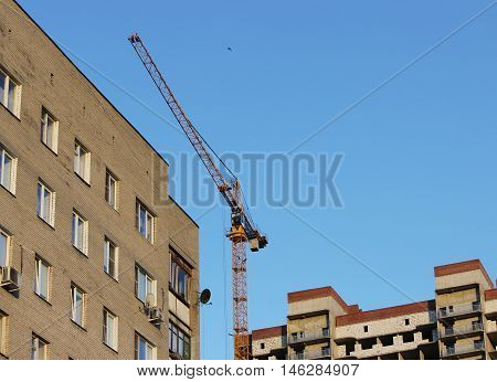 crane and newly built house with windows. wall structure with insulated non-combustible material basalt fiber tiled.