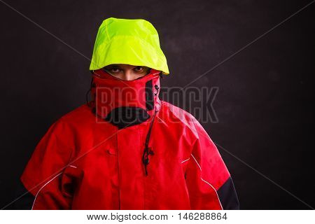Male outdoors man with covered face hood on head. Young man wearing waterproof oilskin. Adventure outdoor action danger concept.