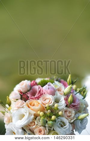 Beautiful wedding white and pink bouquet on a green background