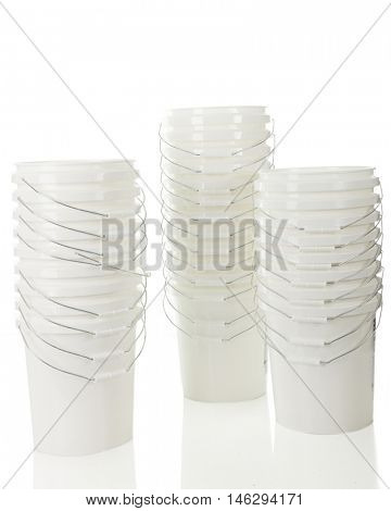 Three stacks of many white plastic buckets, one positions much differently than all the others.  On a white background.