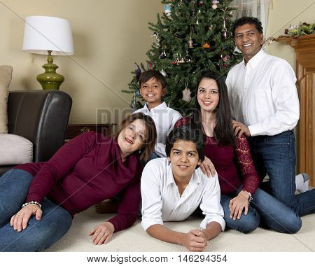 Portrait of a biracial family of five posing before their Christmas tree.