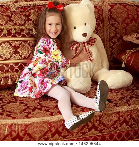 Happy little girl with a long ponytail down to his shoulders, and a red bow on her head, in a beautiful summer dress sitting on the couch. Girl hugging a big Teddy bear.