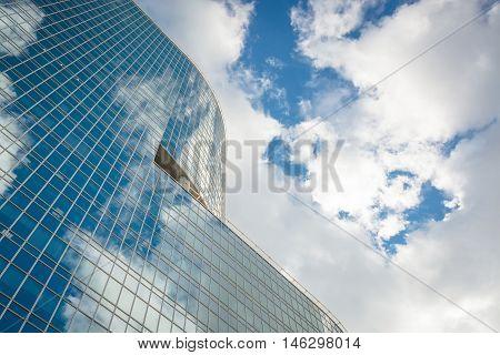 modern glass hi-rise building skyscraper over blue bright sky with clouds