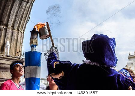 Antigua Guatemala - September 14 2015: Local dressed in colonial costume lights torch from flame in central park during Guatemalan Independence Day celebrations