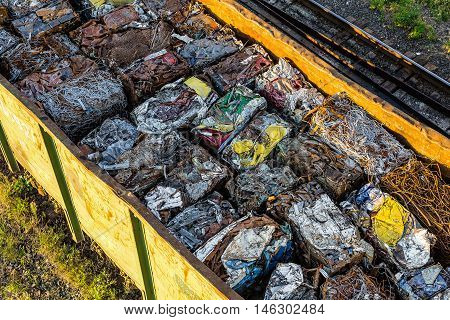 Colorful spracovanie briquettes of various scrap metal in the cargo car of the train