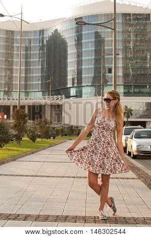 Young girl doing dance step a little bent at the knees in the modern city on the background of a glass building