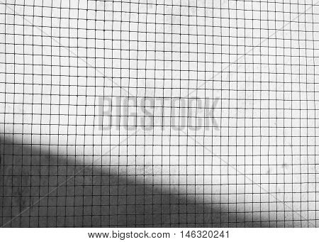 Structure Of Mesh Metal Fence On Dark Cement Wall Background