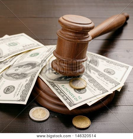 Judge gavel with dollars and euro cents on brown lacquered wooden desk close up. Concept for auction bidding