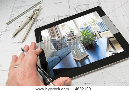 Hand of Architect on Computer Tablet Showing Home Interior Photo Over House Plans, Compass and Ruler.