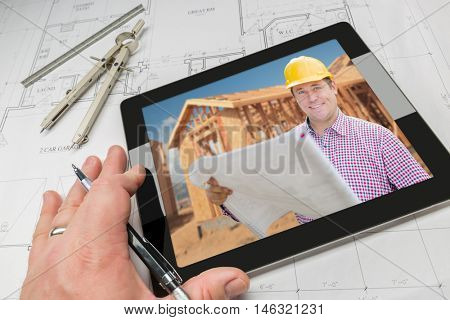 Hand of Architect on Computer Tablet Showing Contractor and Home Framing Photo Over House Plans, Compass and Ruler.