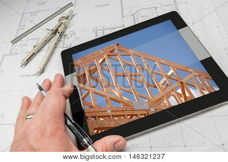 Hand of Architect on Computer Tablet Showing Home Framing Photo Over House Plans, Compass and Ruler.