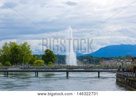 Panoramic view of historic Geneva famous Jet d'Eau fountain at harbor district with blue sky and clouds in summer Canton of Geneva Switzerland