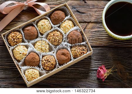 Homemade chocolate truffles in gift box, cup of black coffee and dry rose on wooden table.
