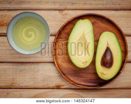 Fresh Avocado And Oil On Wooden Background. Organic Avocado Healthy Food Concept.