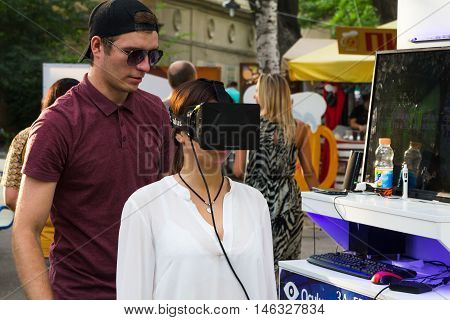 Odesa, Ukraine - August 06, 2016: oung girl trying the oculus virtual reality hemlet at street event in Odesa