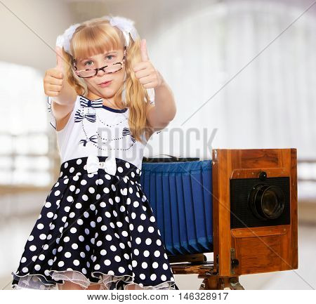 Adorable little blond girl wearing glasses and fancy dress polka dot advertises the old wooden camera.In a room with a large semi-circular window.