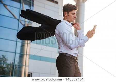 Pensive young businessman holding mobile phone walking with jacket over shoulder outdoors