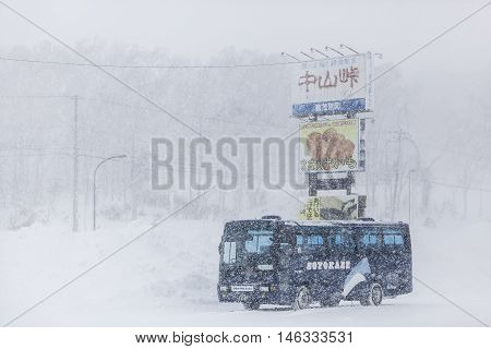 Hokkaido JAPAN - December 13 2011: The large bus is running on the road amid a snowstorm in Hokkaido Japan