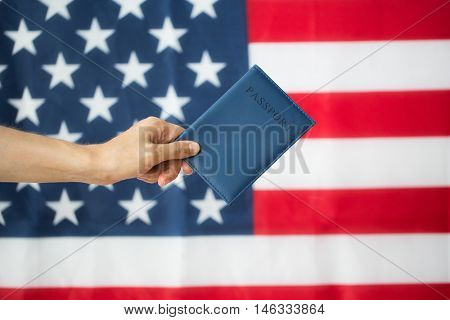 citizenship, patriotism and nationalism concept - close up of hand with american passport