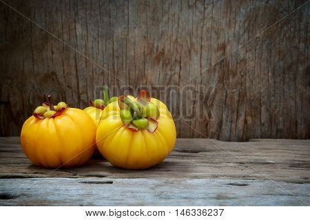 Closeup garcinia cambogia fruit on wood background. Garcinia atroviridis is a spice plants and high vitamin C and hydroxy citric acids (HCA) for diet and good health.