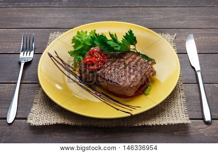 Restaurant food closeup on wood. Perfect juicy beef steak with vegetables and parsley on yellow plate with cutlery. Appetizing meat dish served with sauce, dinner meal. POV poster