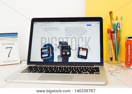 PARIS FRANCE - SEP 8 2016: Apple Computers website on MacBook Pro Retina in a geek creative room environment showcasing new Apple Watch Series 2 with apps and notifications screen