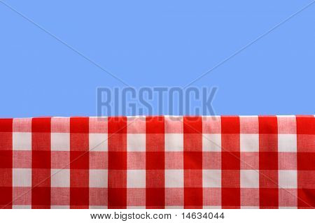 A summertime or springtime picnic background with a gingham tablecoth and a blue sky with ample copy space