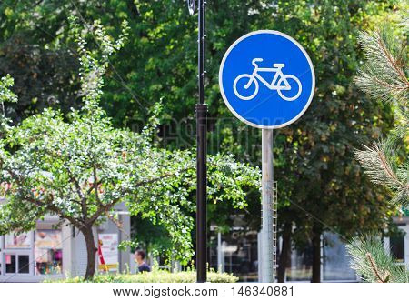 Blue bicycle lane sign with trees background.