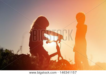 silhouette of little girl riding bike and boy at sunset sky, active kids