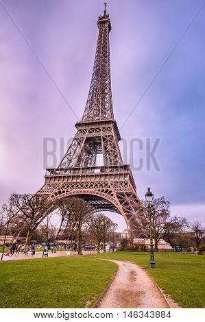 Eiffel Tower and an alley leading to it - Small alley passing through a green grass park leading to the famous Eiffel tower on a rainy day of February. Picture taken in Paris France