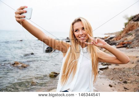 Young smiling beautiful woman showing v gesture and making selfie while standing on the rocky beach