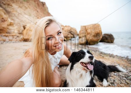 Smiling lovely young woman taking selfie with her dog on the beach
