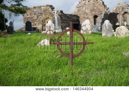 ancient monument and burial concept - old rusty grave cross, headstones and ruins on celtic cemetery graveyard in ireland