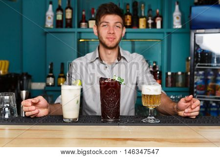 Young handsome Barman offers exotic sweet non-alcoholic cocktails in restaurant. Professional bartender at work in bar made refreshing drinks. Selective focus on glasses of cream soda and berry mix