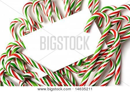 A white notecard, greeting card, or invitation surrounded by brightly color Christmas Candy Canes with copy space poster