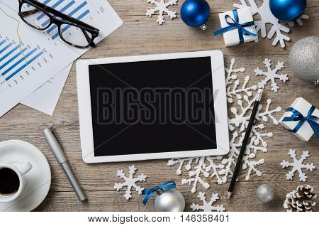 High angle view of digital tablet with black screen on wooden desk with christmas decorations. Top view of digital tablet with business document in a xmas atmosphere with snowflakes.