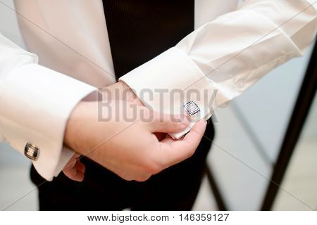 Groom is wearing cuff-links indoors. Male portrait of handsome guy. Beautiful model boy in colorful wedding clothes. Man is posing