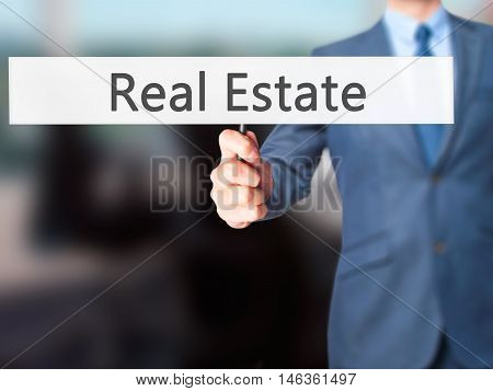 Real Estate - Businessman Hand Holding Sign