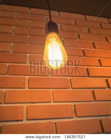 Classic light bulb and brick wall background.