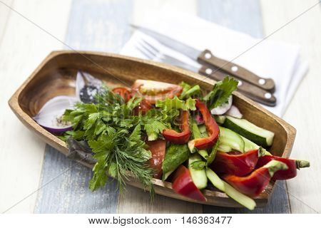 Fresh vegetables on a wooden plate with fork and knife. Red pepper, tomato, cucumber, radish, parsley, dill healthy diet