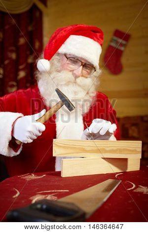 Santa Claus working with hammer and wood at the table
