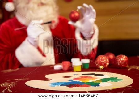 Closeup of paint palette with Santa Claus drawing in background